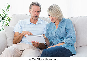 Couple using tablet together on the sofa