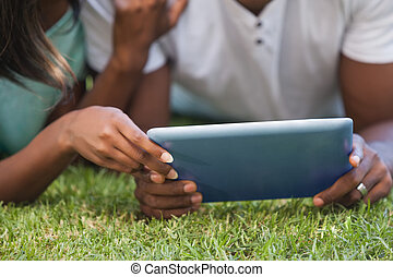 Couple using tablet together outside