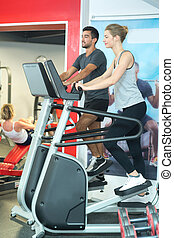 couple using the step machine at the gym