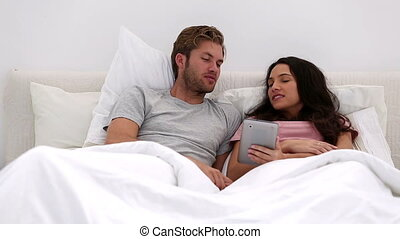Couple using their tablet together and chatting in bed at...