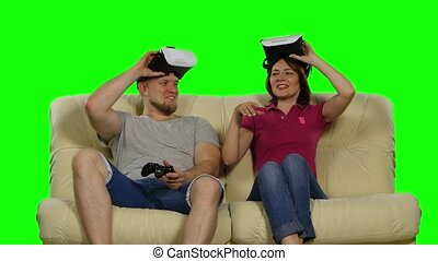 Couple using VR glasses sitting on the sofa. Green screen