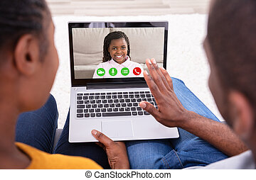 Couple Video Conferencing With Their Daughter On Laptop