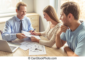 Couple visiting realtor - Handsome middle aged realtor in...