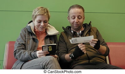 Family couple waiting for a flight at the airport terminal talking smiling laughing and checking up passports and tickets. 4K UHD video footage.