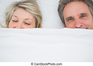 Couple waking up under the covers at home in bed