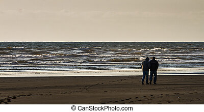 Couple Walk Along the Beach together