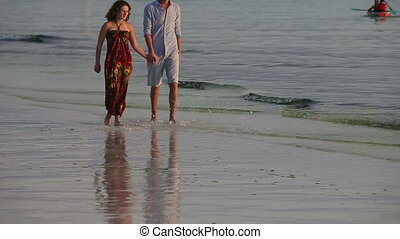 Couple walk together along the beach at sunset