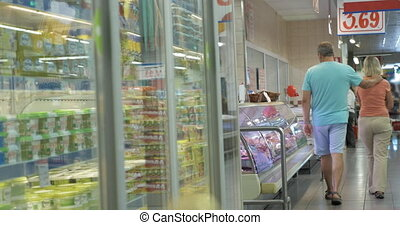 Couple Walking along the Fridges in Supermarket