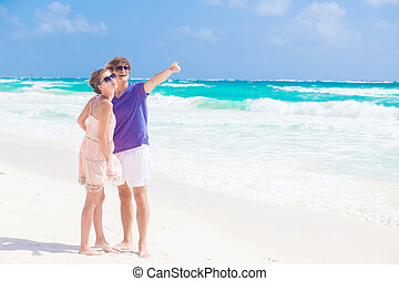 Couple walking and having fun on a tropical beach at Maldives