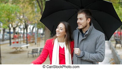 Front view of a happy couple walking towards camera and pointing away under the rain in winter