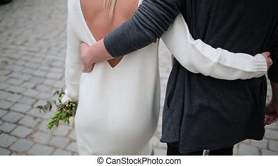 Couple walking arm in arm on the pavement