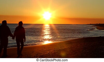 Senior adult couple holding hands walk up the beach as the sun is about to set on the horizon.