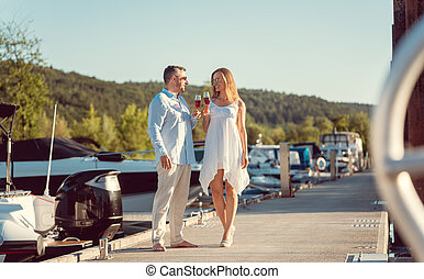 Couple walking between the boats on a river port