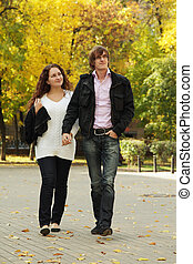 Couple walking by autumn park