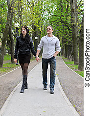 Couple walking down the road in the park.