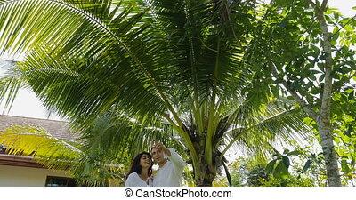 Couple Walking Embracing In Tropical Garden Near Villa...