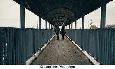 Couple walking hand-to-hand across the footbridge over highway