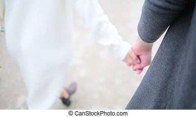 Couple walking holding hands close up
