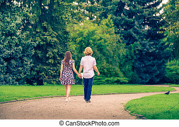 Couple walking holding hands in park