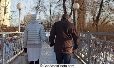 Couple walking holding hands on a small bridge near catherdral. 4K steadicam video