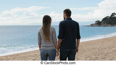 Couple walking holding hands on the beach