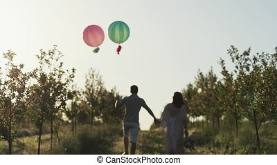 Couple walking in a apple garden and holding hands at sunrise