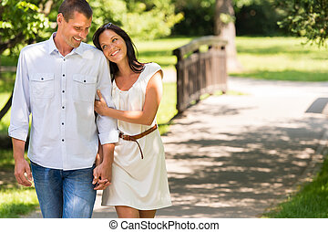 Couple walking in park hand in hand - Smiling couple walking...