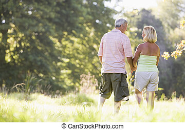Couple walking in park holding hands