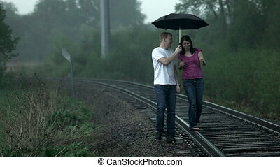 Couple walking in rain - Young couple (man and woman),...