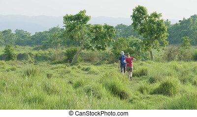 Couple walking in rainforest park in Chitwan, Nepal. -...