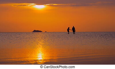 Couple walking in sea at sunset