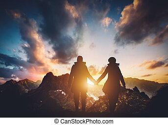 Couple walking in the mountains during sunset.
