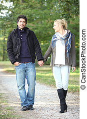 couple walking in the park hand in hand