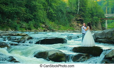 Couple walking near the mountain river on a spring day