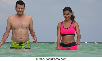 Couple Walking Ocean Water Wearing Bathing Suits