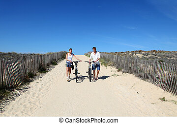 Couple walking on a sandy path with bicycles