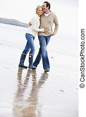 Couple walking on beach arm in arm smiling