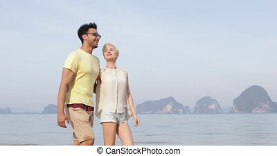 Couple Walking On Beach Embracing Talking, Man And Woman...