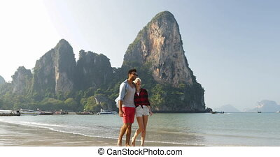 Couple Walking On Beach Embracing Young Man And Woman...