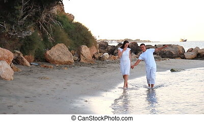 Couple walking on beach. Young happy interracial couple walking on beach