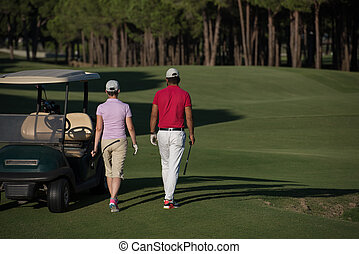 couple walking on golf course - young couple walking to next...