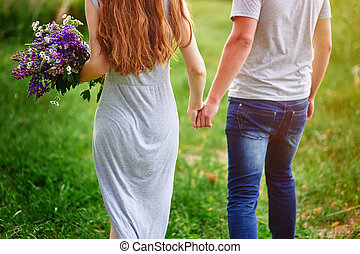 couple walking on meadow with bouquet of flowers