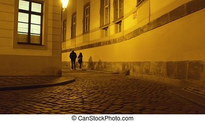 Couple walking on old town street in Prague at night. 4K steadicam video