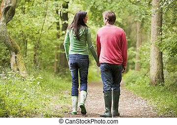 Couple walking on path holding hands