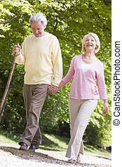 Couple walking on path in park holding hands and smiling