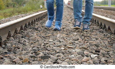 Couple walking on railroad tracks - Man and woman walking...