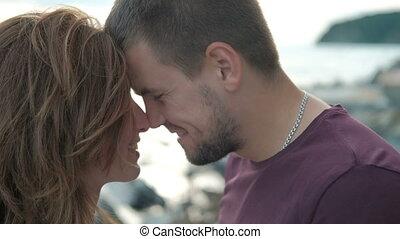 Couple walking on sea shore looking into distance, tender hugs.