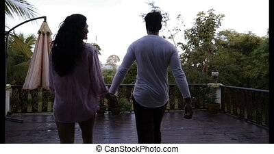 Couple Walking On Summer Terrace Holding Hands Back Rear View Enjoying Landscape Of Sunrise In Tropical Forest Mix Race Man And Woman Outdoors In Morning
