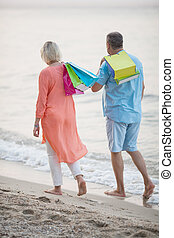 Couple walking on the beach after vacation shopping