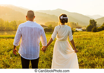 Couple walking on the field with sunset view